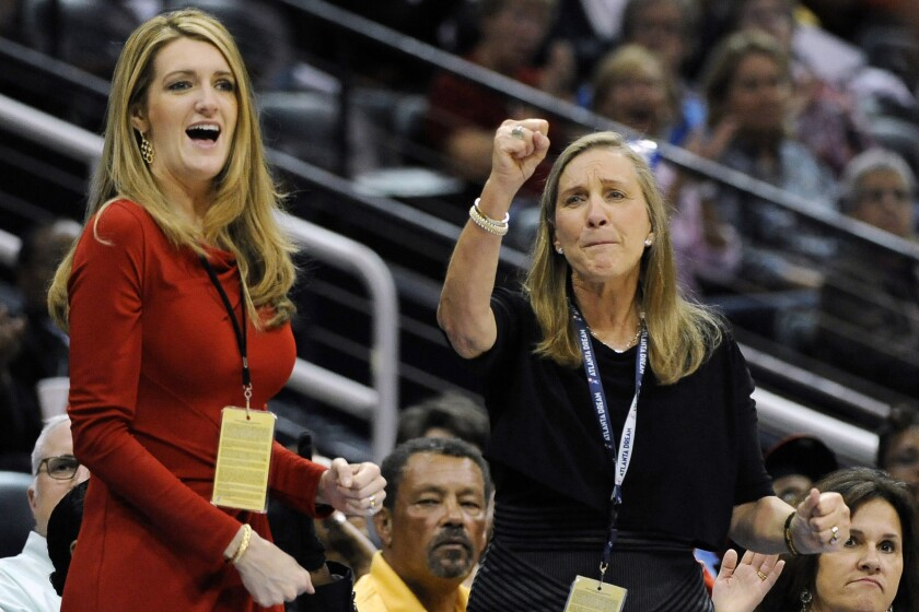 FILE-In this Tuesday, Sept. 6, 2011 file photo, Mary Brock, right, and Kelly Loeffler cheer from their courtside seats as the Atlanta Dream basketball team plays in the second half of their WNBA basketball game, in Atlanta. Republican donor and financial services executive Loeffler tapped by Georgia governor Kemp for U.S. Senate seat as three-term Republican Sen. Johnny Isakson, who is stepping down because of health issues. (AP Photo/David Tulis, File)