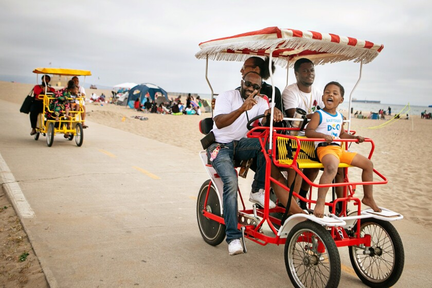 Families ride pedal cabs at the beach.