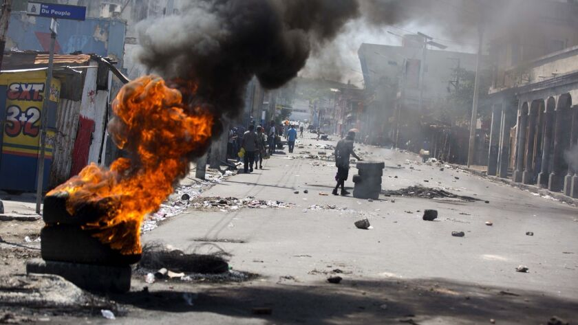Tires burn at a road block set up by anti-government protesters downtown during a general strike in