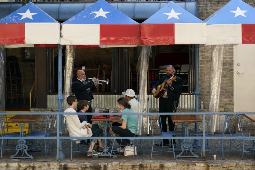 Dos mariachis tocan para comensales en un restaurante junto al río en San Antonio, Texas