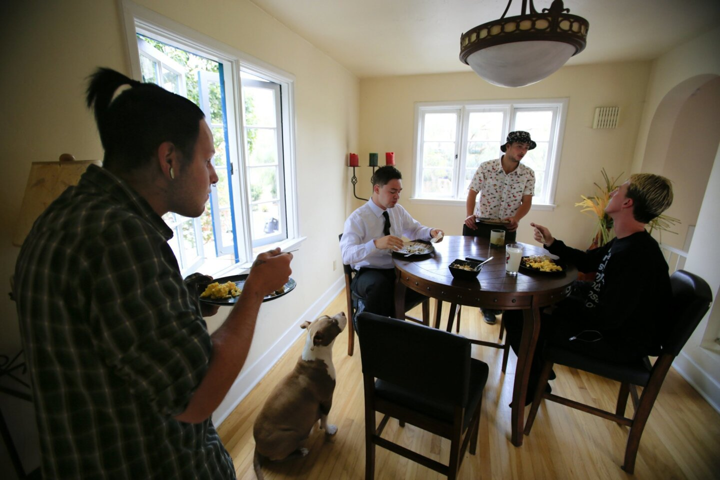 Blu Tomson, Ian Roehling, and Nick Wiggins, who are homeless, talk with Nick Adams, the house manager at the Urban Street Angels six bed men's home, one of two the homeless outreach organization runs.