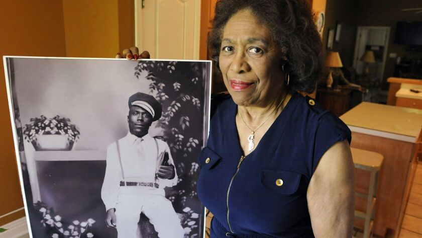 Josephine Bolling McCall shows a photo of her father, Elmore Bolling, one of thousands of lynching victims remembered at the new National Memorial for Peace and Justice.