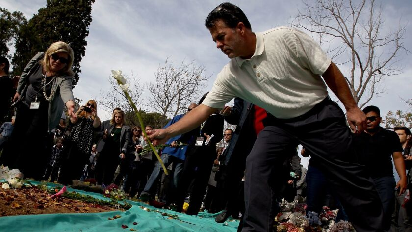 Dozens of mourners leave flowers following a mass burial of L.A. County's unclaimed dead at the county cemetery in Boyle Heights in December 2015.