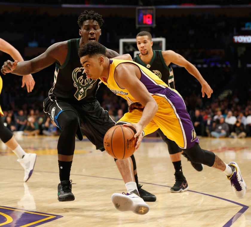 Lakers' D'Angelo Russell dribbles past Milwaukee's Johnny O'Bryant III during the first half of a game at Staples Center on Tuesday.