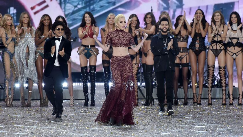 Standing in front of the Victoria's Secret models, Bruno Mars, left, Lady Gaga and the Weeknd appear on stage in Paris.