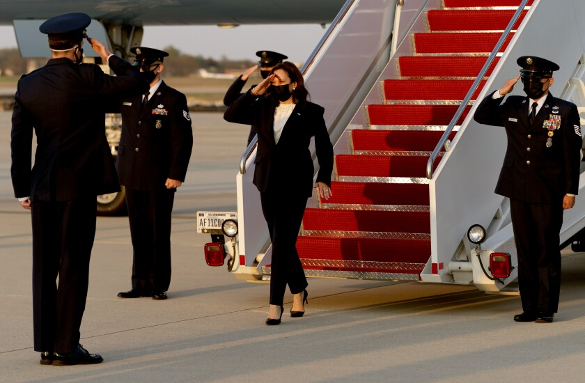 Kamala Harris salutes as she exits a plane with military members in uniform nearby