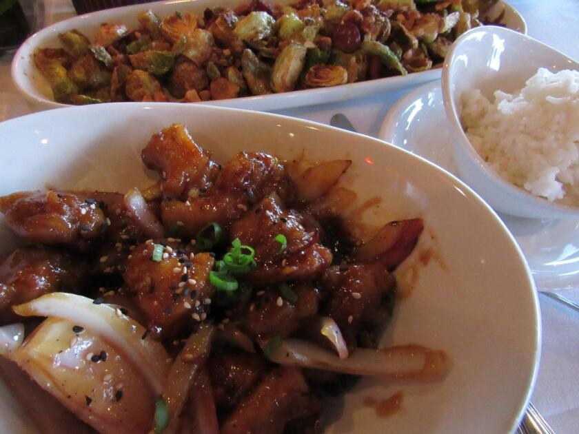 Korean Chicken at Bali Hai restaurant is served with a house-made sauce, onions and rice.