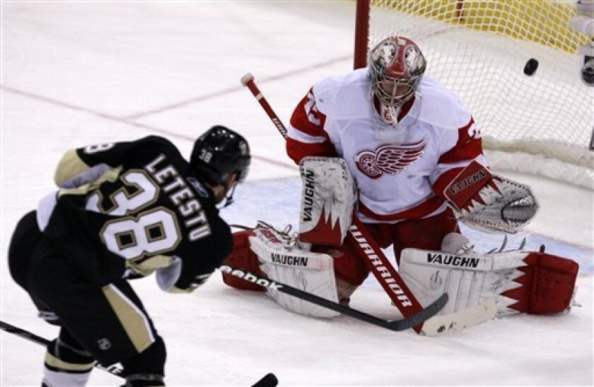 Detroit Red Wings goalie Jimmy Howard, right, blocks a first-period shot by Pittsburgh Penguins' Mark Letestu (38) during an NHL hockey game in Pittsburgh, Sunday, Jan. 31, 2010. (AP Photo/Gene J. Puskar)