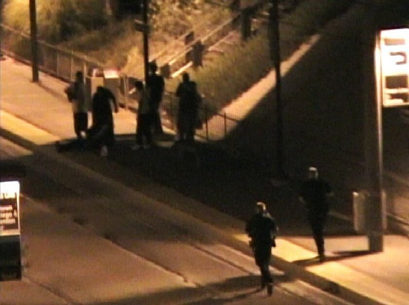 Two police officers run to the spot in the Grossmont Trolley Station where a transit security guard was shot by a robber on Saturday, July 18, 2009. Still image taken from home video.
