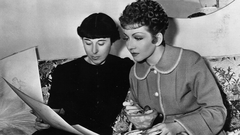 Claudette Colbert takes a lunch break to discuss her costumes with designer Edith Head.