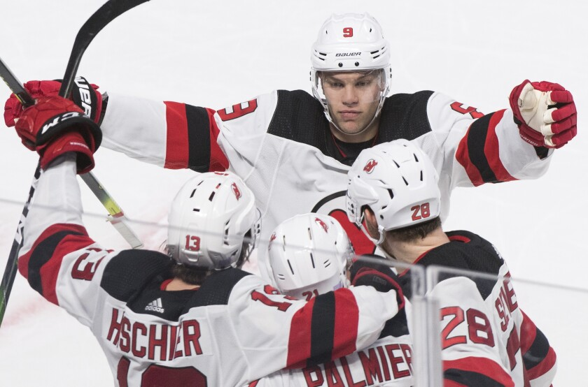 New Jersey Devils' Kyle Palmieri (21) celebrates with teammates Taylor Hall (9), Nico Hischier (13) and Damon Severson (28) after scoring against the Montreal Canadiens during overtime in an NHL hockey game in Montreal, Saturday, Nov. 16, 2019. (Graham Hughes/The Canadian Press via AP)