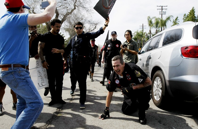 """Protesters taunt an injured Ku Klux Klansman after members of the KKK tried to start a """"White Lives Matter"""" rally at Pearson Park in Anaheim. Witnesses said the Klansmen used the point of a flagpole as a weapon while fighting with protesters."""