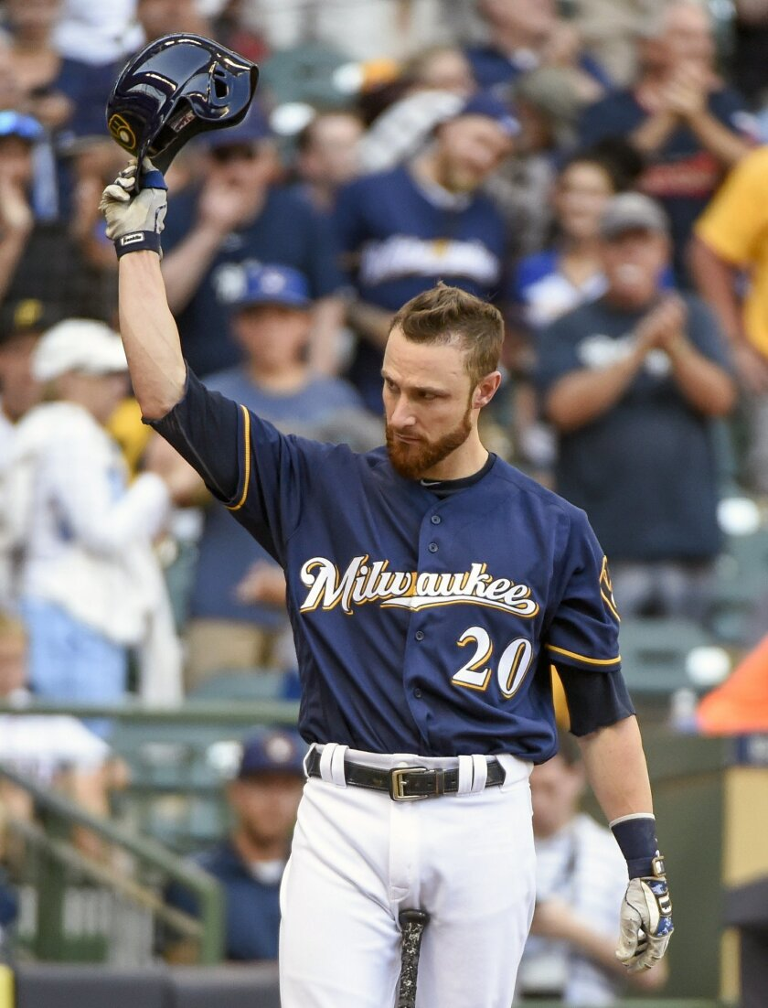 Milwaukee Brewers' Jonathan Lucroy tips his batting helmet after getting a standing ovation from fans while pinch-hitting during the eighth inning of a baseball game Sunday, July 31, 2016, in Milwaukee. Lucroy has blocked his proposed trade to the Cleveland Indians. Lucroy said Sunday, July 31, 201
