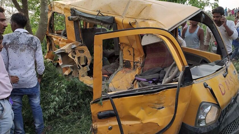 The mangled remains of a school van after it collided with a train in Kushinagar district in Uttar Pradesh, India.
