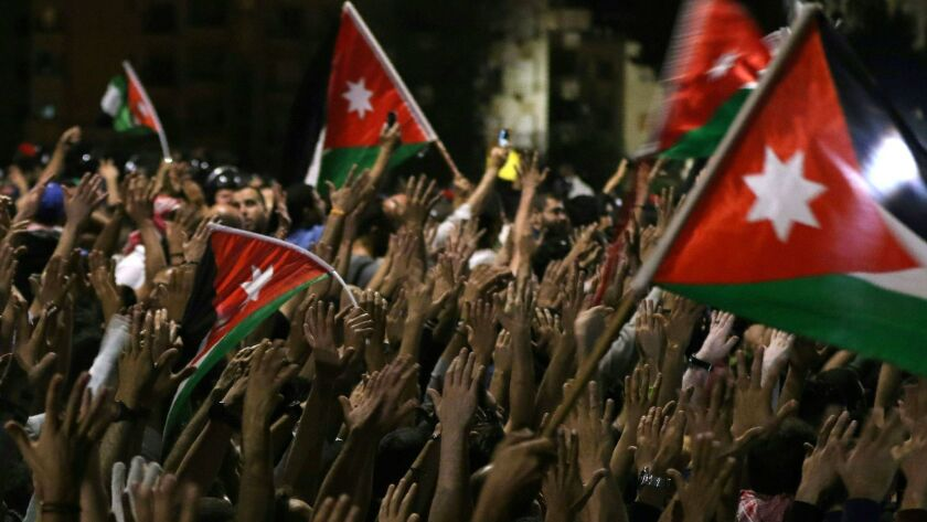 Protesters raise their hands and wave flags near members of the gendarmerie and security forces during a demonstration outside the prime minister's office in Amman, Jordan's capital, late on June 3, 2018.