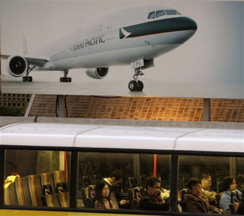 A bus passes by a commercial Cathay Pacific billboard in Hong Kong Thursday, Jan. 8, 2009. Shares in Cathay Pacific Airways Ltd. fell sharply Thursday after Asia's third-largest carrier said it could lose nearly $1 billion from hedging its jet fuel costs, adding to the toll on global airlines from