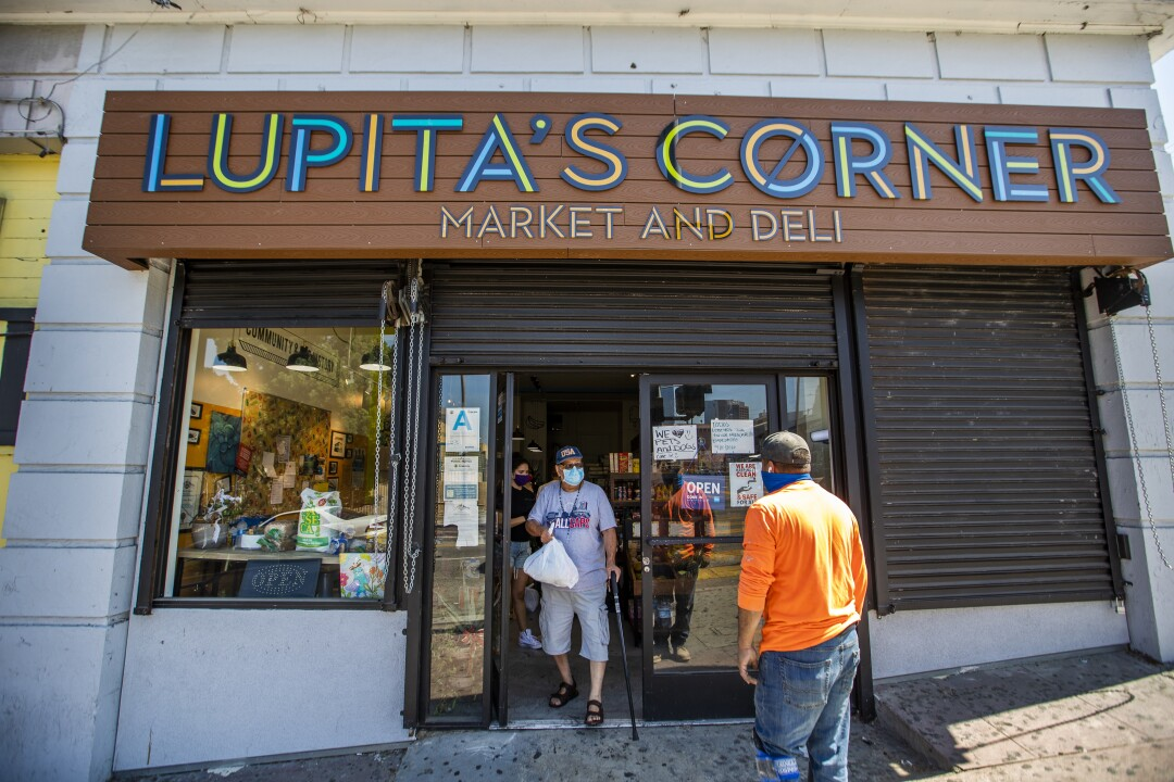 A neighborhood resident receives donated groceries at Lupita's market.