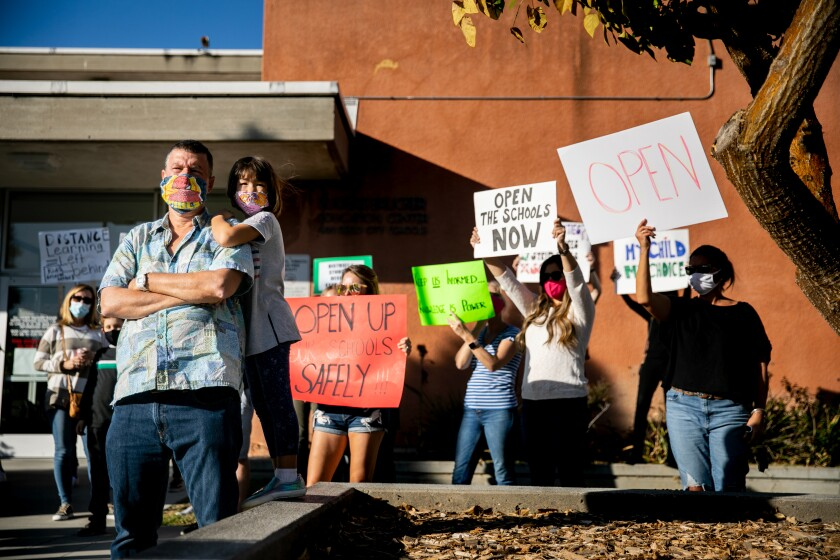 Edward Ewing and daughter Sky Ewing join protesters Oct. 27 outside the San Diego Unified headquarters.