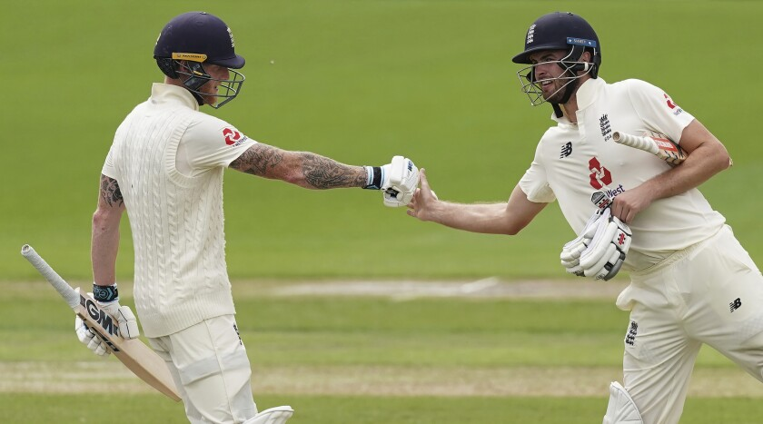 England's Ben Stokes, left, fist bumps teammate Dom Sibley to celebrate scoring 150 runs during the second day of the second cricket Test match between England and West Indies at Old Trafford in Manchester, England, Friday, July 17, 2020. (AP Photo/Jon Super, Pool)