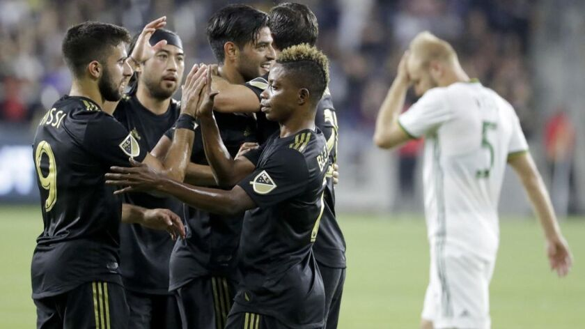 LAFC players celebrate a goal by forward Marco Urena against the Portland Timbers during the first half of a match on July 18.