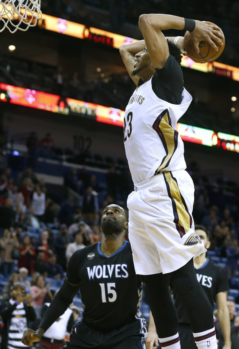 New Orleans Pelicans forward Anthony Davis goes in for a dunk as Minnesota Timberwolves forward Shabazz Muhammad (15) watches during the second half of an NBA basketball game Tuesday, Jan. 19, 2016, in New Orleans. The Pelicans won 114-99. (AP Photo/Jonathan Bachman)