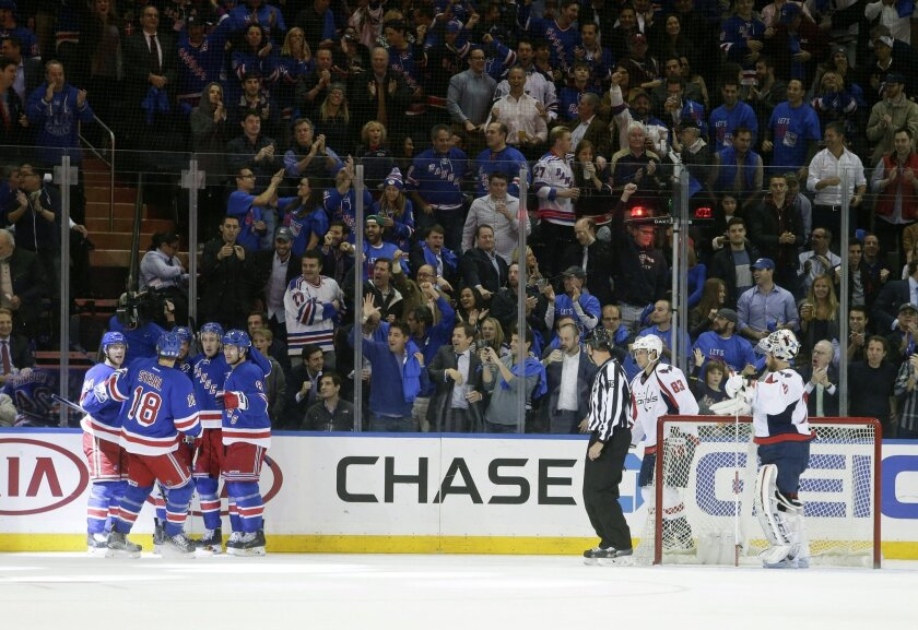Washington Capitals goalie Braden Holtby (70) and Jay Beagle (83) watch as the New York Rangers celebrate a goal by Kevin Hayes during the first period of an NHL hockey game Tuesday, Nov. 3, 2015, in New York. (AP Photo/Frank Franklin II)
