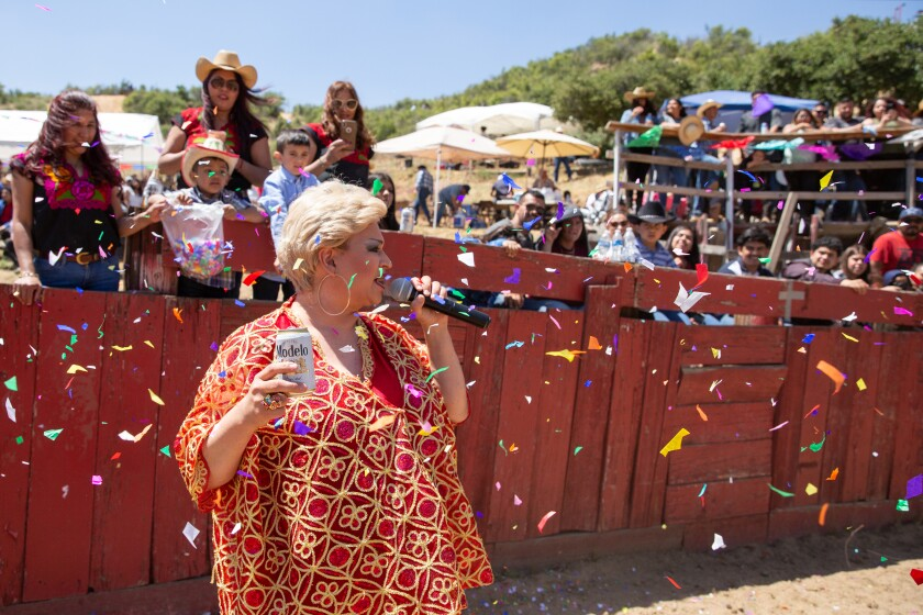 Towne, holding a beer given to her by an audience member, performs as Paquita la del Barrio inside a bullring at a festival in San Bernardino.