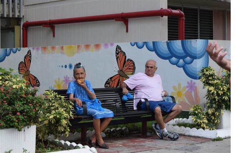 Dos ancianos comparten una silla en Miami, Florida. EFE/ARCHIVO