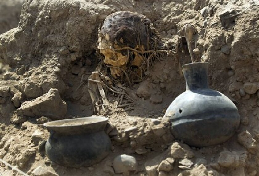 An excavated skull and artifacts lay unearthed at the sports complex where Peru's national soccer team practices in Lima, Peru, Tuesday, Feb. 26, 2013. According to Peru's Ministry of Culture, 11 pre-Inca tombs belonging to the Lima culture (200-700 AD) and Yschma (1100-1400 AD) were located inside