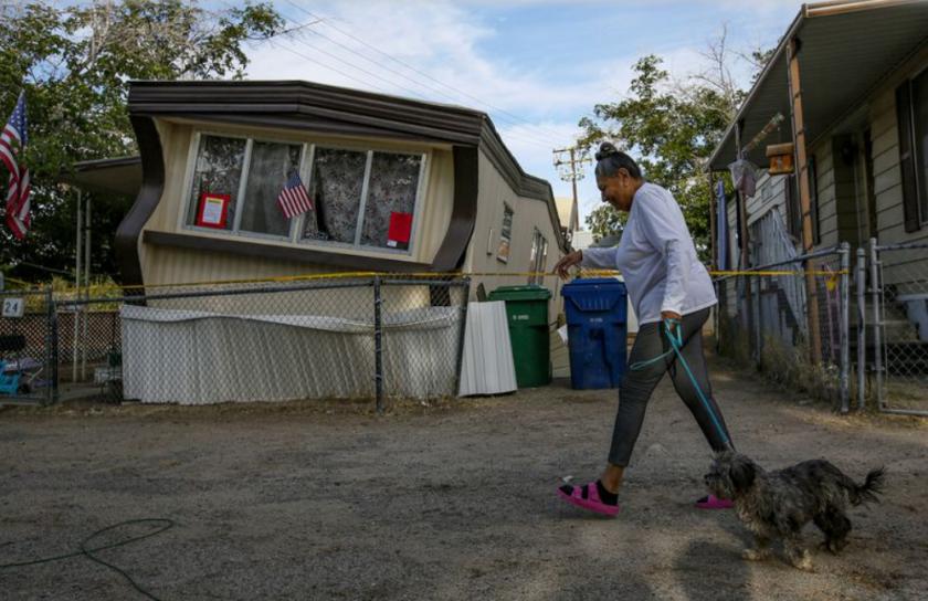 Carmen Rivera, de 65 años, pasa frente a una casa móvil dañada por el terremoto del jueves en Ridgecrest. (Irfan Khan / Los Angeles Times)
