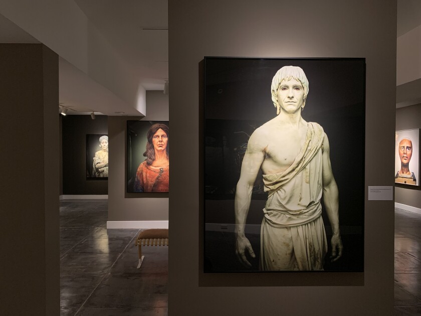 A gallery with photos of people decorated as sculptures