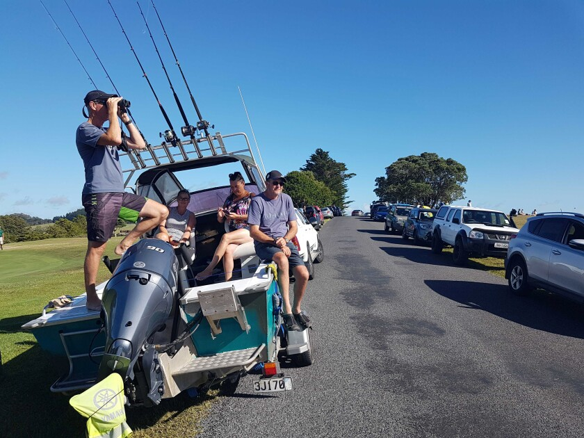 A man looks through binoculars while standing in a boat with other people on a road with parked cars