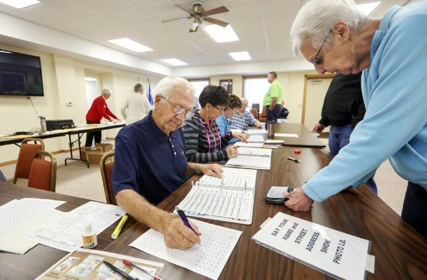 John Richard, left, checks in voters on election day at Jamestown Town Hall in Kieler, Wis., on Tuesday, Nov. 8.