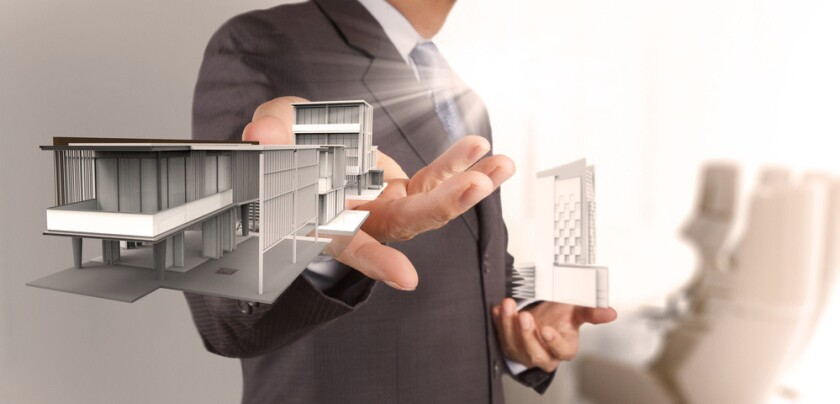 businessman hand presents house model on modern computer as delvelopment concept