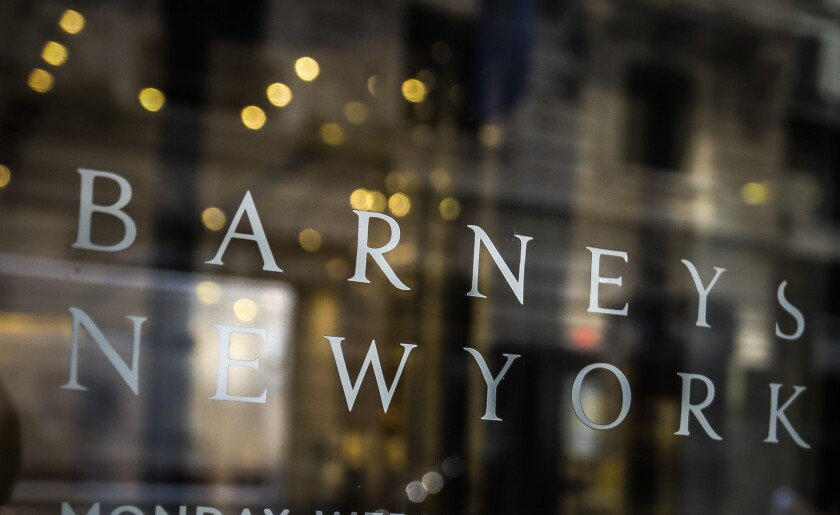 FILE - In this July 16, 2019, file photo signage for Barneys New York department store is displayed on the store's window in New York. Barneys New York says a bankruptcy judge has approved the sale of its assets to fashion licensing company Authentic Brands Group. The New York-based retailer said Thursday there's still a chance that rival bidders could come forward before the sale closes on Friday. (AP Photo/Bebeto Matthews, File)
