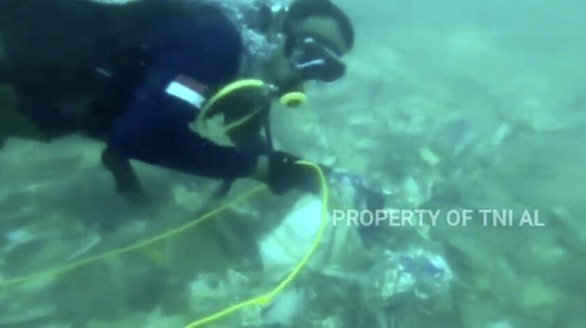 Divers recovering debris strewn on the sea floor in Java Sea