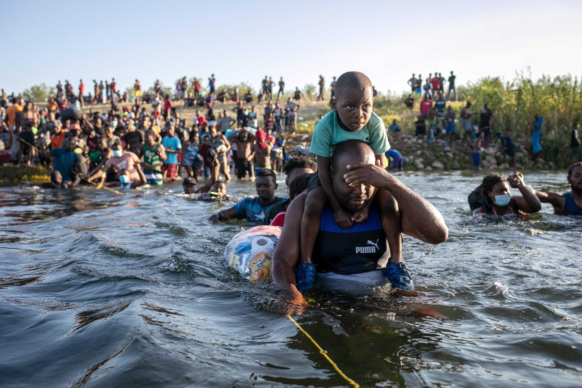 A man shields his face as he crosses the Rio Grande with a youngster on his shoulders.