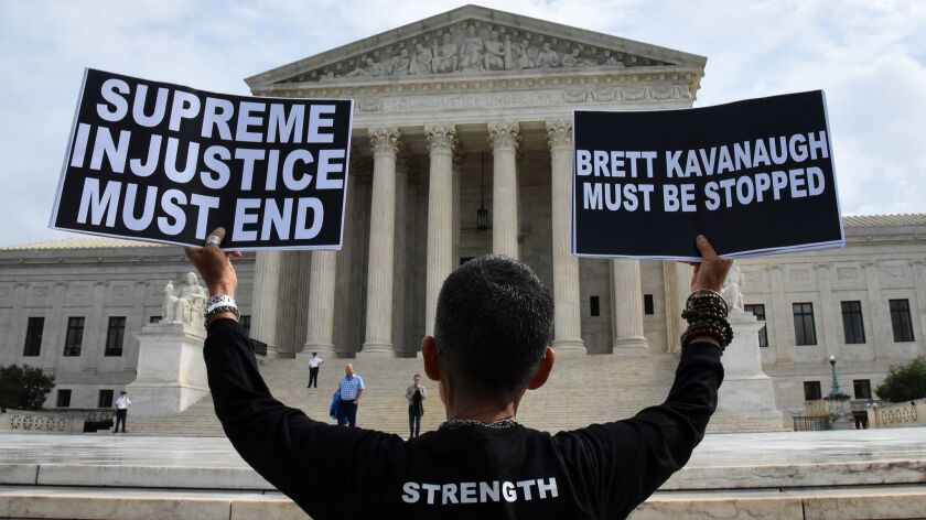 A demonstrator opposed to Brett Kavanaugh holds signs in front of the U.S Supreme Court on Sept. 25.