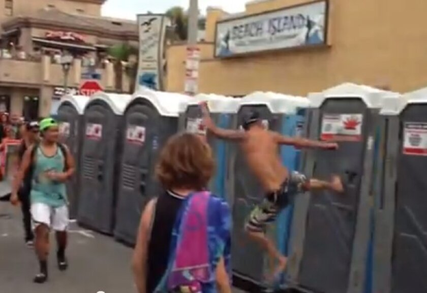 A screen shot of a video showing people toppling portable toilets in Huntington Beach Sunday.