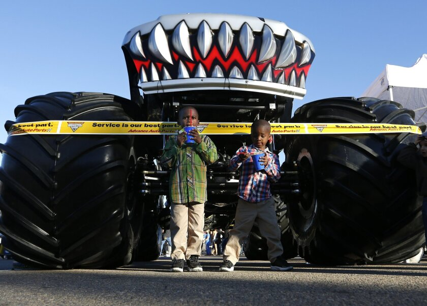 """Kymondre Jones, (left) and Traville Jones, 5, chill out with their snow cones in front of the Monster truck """"Hot Wheels"""" at the Monster Jam Pit Party at Qualcomm Stadium."""