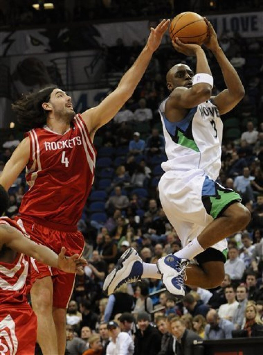 Minnesota Timberwolves' Damien Wilkins, right, shoots as Houston Rockets' Luis Scola tries to block in the first half of an NBA basketball game Saturday, March 6, 2010, in Minneapolis. (AP Photo/Jim Mone)