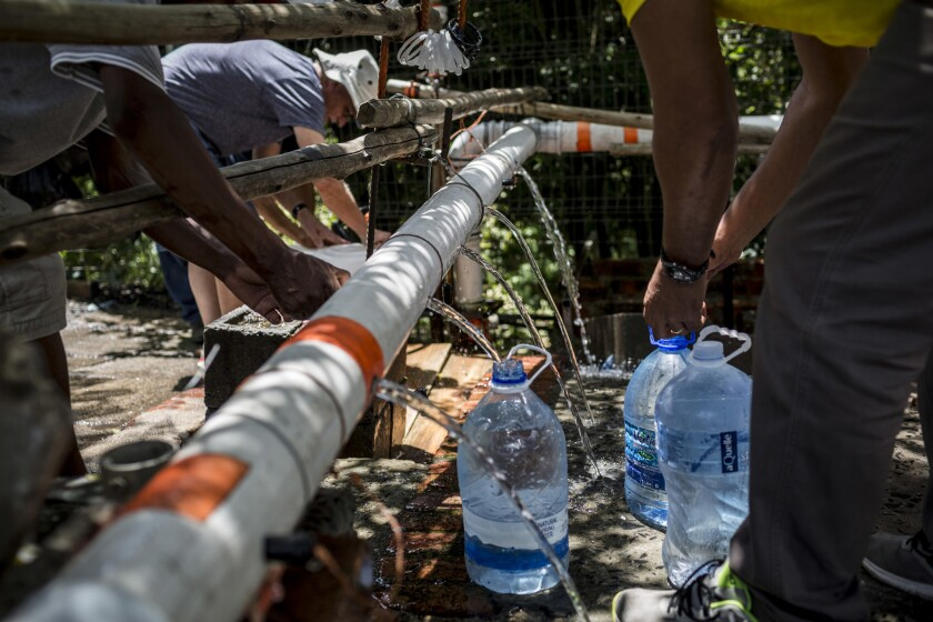 People refill water bottles Feb. 14, 2018, at the Newlands Spring tap. Cape Town residents have been reducing their water usage ahead of a potential Day Zero, originally expected in April; thanks to conservation, that has been pushed back to July.
