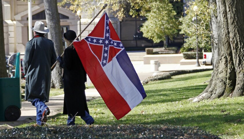 FILE - In this Jan. 19, 2016 file photo, a couple leaves the grounds of the state Capitol in Jackson, Miss., after participating in a rally in support of keeping the Confederate battle emblem on the state flag. In Mississippi, the last state to display the Confederate battle emblem on its flag, som