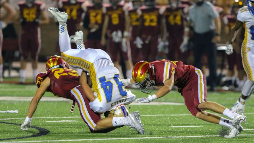 San Pasqual's Mark Santar is upended by Torrey Pines tacklers Luke Mikolajewski (left) and Tyler Wheeler in the Falcons' 35-0 nonleague win Friday night.