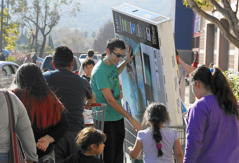 A customer leaves the Best Buy store in Los Feliz with his new big-screen television on Black Friday in 2014.