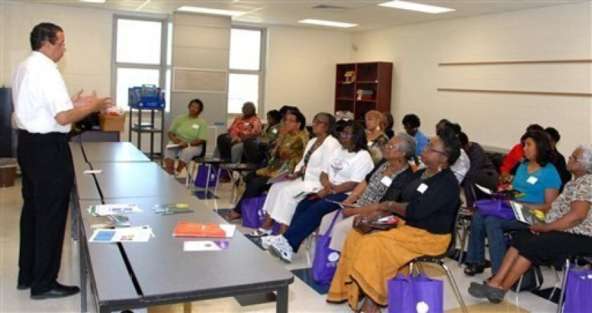 In this image made available by AARP shows Wallace Cunningham, left, AARP South Carolina Associate State Director for Multicultural Outreach presenting a workshop on the Affordable Health Care Act on Saturday, Sept. 7, 2013 in Bishopville, S.C. Federal Health Officials are assuring medicare recipients that their benefits will not change when the Affordable Care Act starts. Many are confused by overlapping enrollment periods for Medicare and the Affordable Care Act. (AP Photo/AARP)