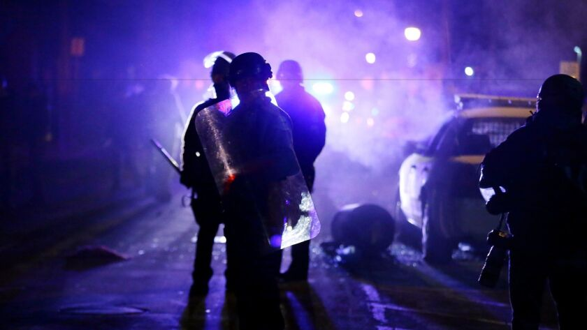 On Nov. 25, 2014, police officers watch protesters as smoke fills the streets in Ferguson, Mo.