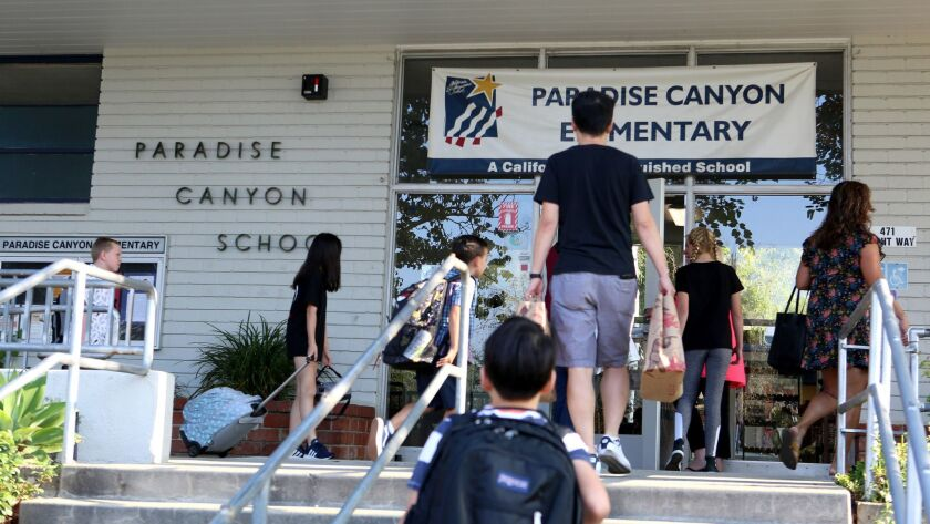Students and parents loaded with school supplies arrive on the first day of school at Paradise Canyo