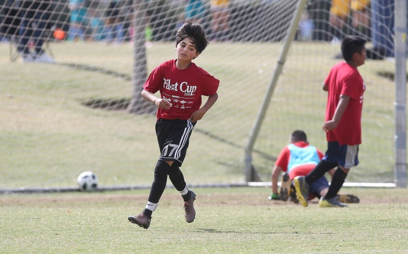 Costa Mesa Adams player Christian Sotomayor, trots upfield after a goal against Kaiser in a boys'