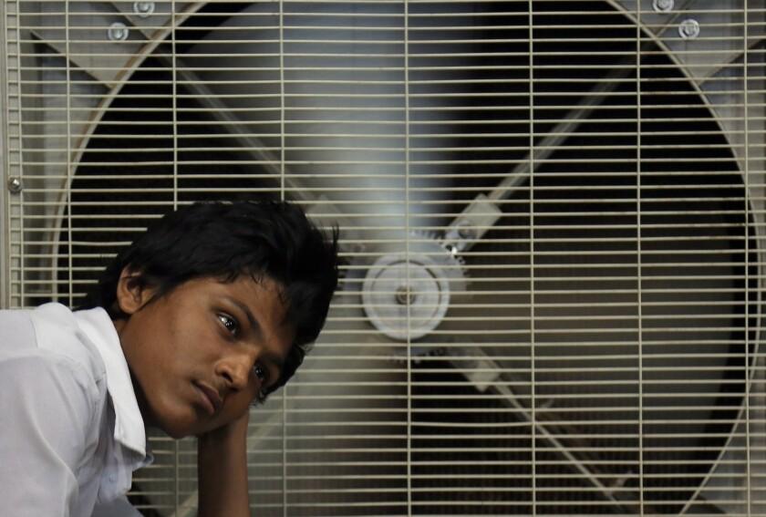 Un hombre descansa ante un ventilador para aliviar su calor en Hyderabad, India.